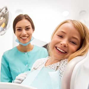 A young girl and her dental hygienist smile after receiving a fluoride treatment