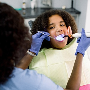 A dental hygienist uses a curing light to bond the tooth-colored filling into place on a young girl's smile