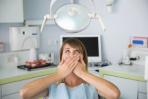 Fearful dental patient covering her mouth