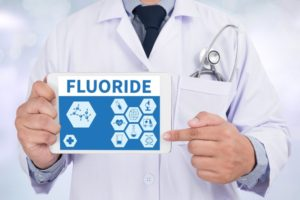 dentist pointing to fluoride for adults in East Islip on tablet