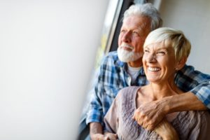Smiling older couple following East Islip dentist healthy tips