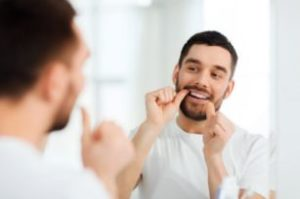 Man flossing with tips from a dentist in East Islip