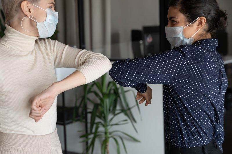 Two women doing an elbow bump