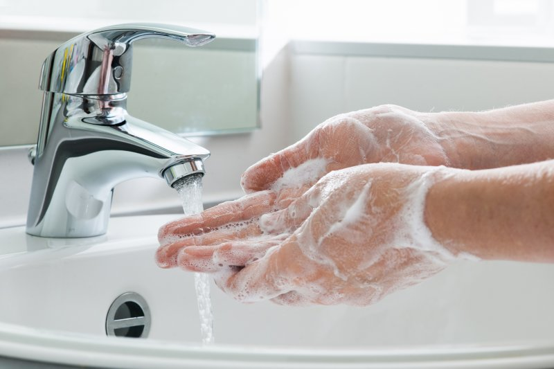 a person washing their hands with soap and water at the sink