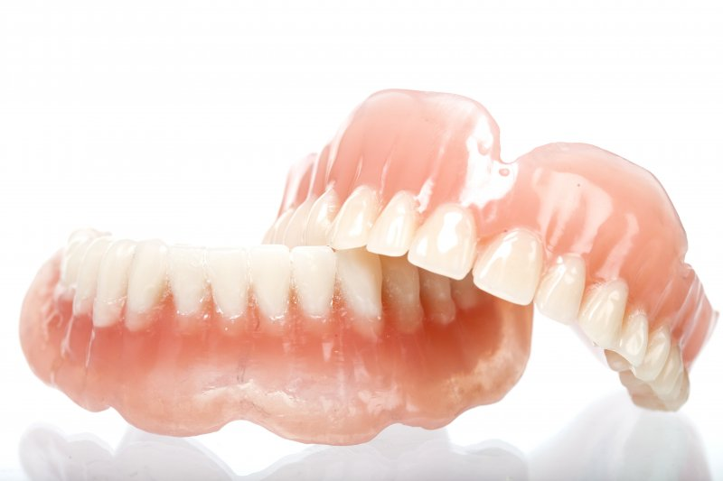 an up-close view of an upper and lower denture for a patient's smile