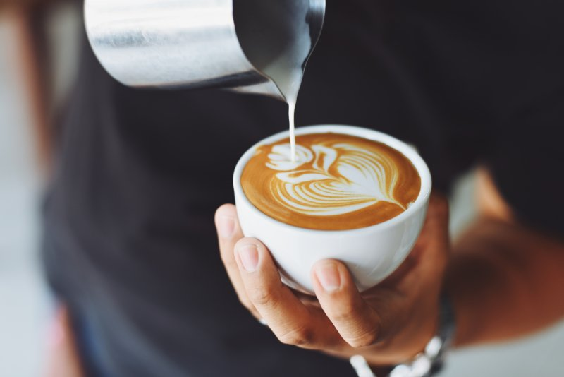 Man pouring creamer into cup of coffee
