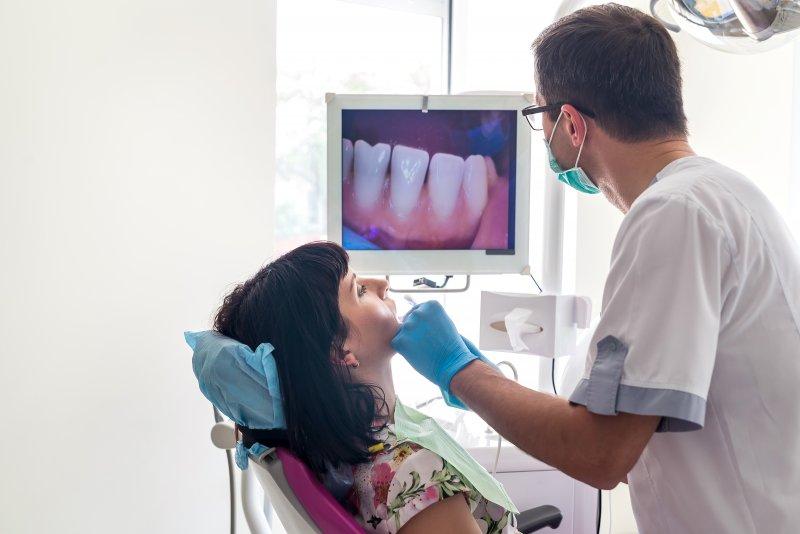 Dentist using intraoral camera to examine patient's mouth