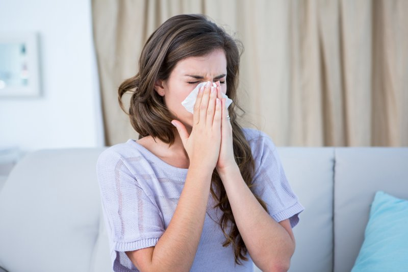 woman blowing her nose because of allergies