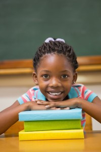 Smiling pupil sitting at her desk