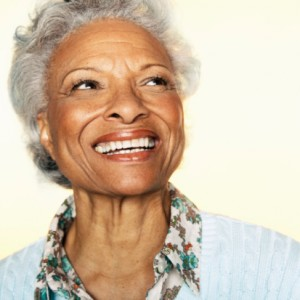 senior woman with a beautiful dental implant supported denture from the dentist Islip loves